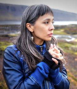 A photograph of Dao Strom in a blue coat, in front of out-of-focus landscape of moss and mountains.