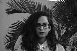 A black and white photograph of poet Aditi Machado, wearing glasses, in front of palm leaves.