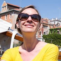 This is a sunny portrait of the Rail's Art Editor, Amanda Gluibizzi with houses in the background and a blue sky. Gluibizzi is wearing a yellow shirt and sunglasses.