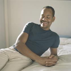 This is a photo of Artist Lyle Ashton Harris in a room leaning on a bed. The background is off-white and Harris's shirt is dark green.