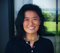 This is a headshot of Rail Board Member, Helen Lee with a window background overlooking a garden.