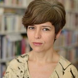 A photo of poet and writer Mónica de la Torre in front of bookshelves.